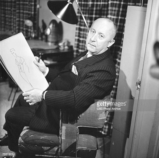 French fashion designer Christian Dior sits in a chair with a sketchpad, on which is a fashion design, for a broadcast of the CBS celebrity interview...