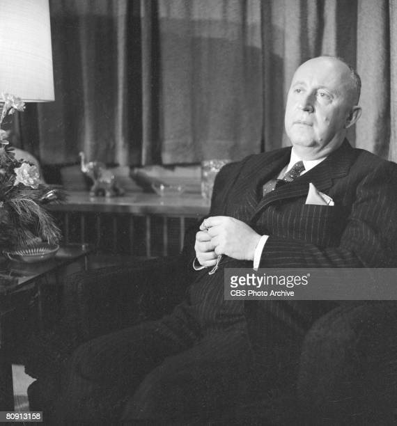 French fashion designer Christian Dior sits in an armchair at his home during an appearance on the tv show 'Person to Person' November 7 1955