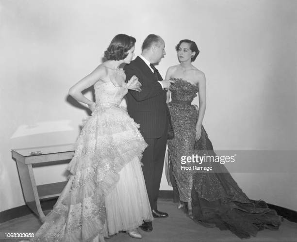 French fashion designer Christian Dior with two of his models at a show of ninety new Dior creations at the Savoy hotel, London, 24th April 1950....