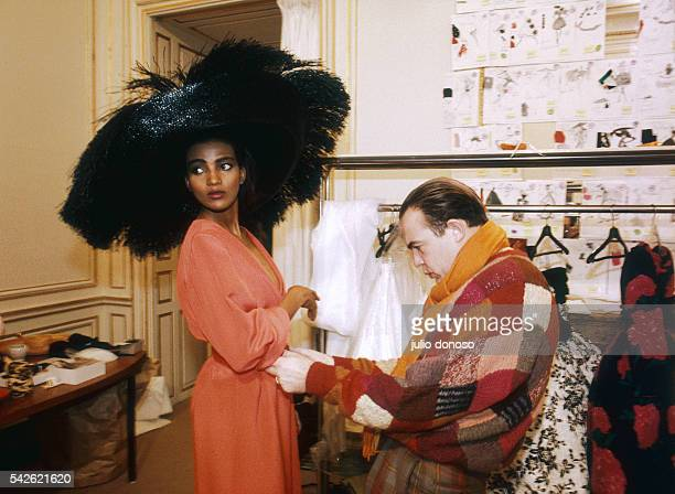 French fashion designer Christian Lacroix works on his 1987 springsummer haute couture line for Patou Fashion model Kadija is wearing a large black...