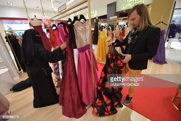 French fashion designer Christophe Guillarme checks a dress during the Arab Fashion Week in the Gulf emirate of Dubai on November 19, 2017. / AFP...