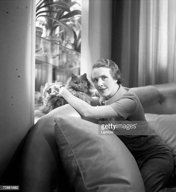 French fashion designer countess MarieBlanche de Polignac daughter of designer Jeanne Lanvin sits on a couch with a pet cat France July 1934
