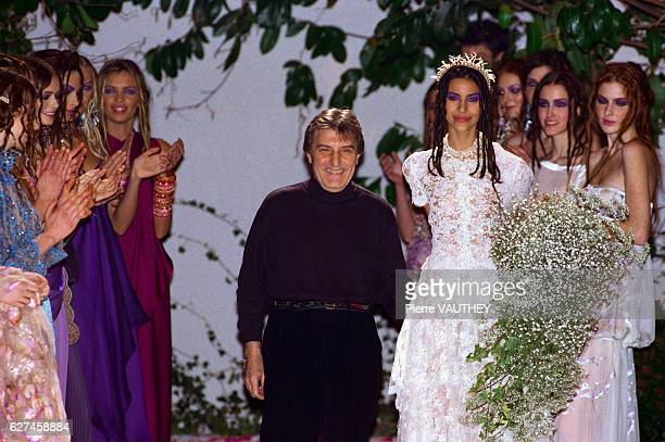 French fashion designer Emanuel Ungaro taking a bow with models wearing a wedding dress and evening gowns designed by Ungaro at the Ungaro...