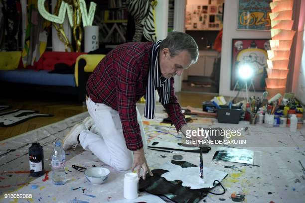 French fashion designer JeanCharles de Castelbajac is pictured as he paints during a photo session in his studio in Paris on February 1 2018 SAKUTIN
