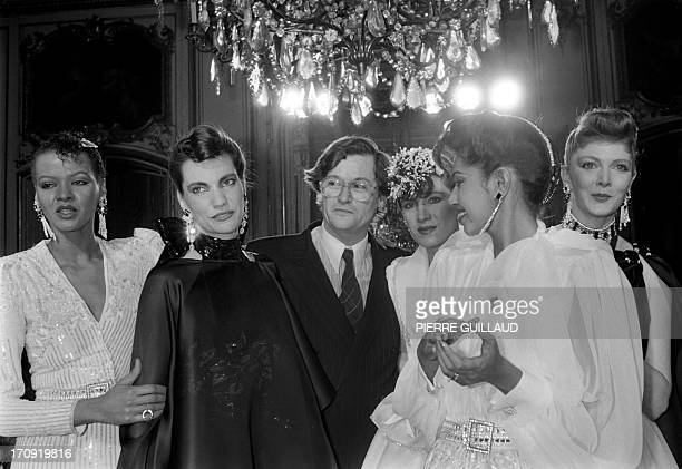 French fashion designer JeanLouis Scherrer is congratulated by models in Paris on January 24 1983 after presenting his springsummer haute couture...