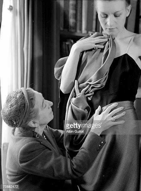 French fashion designer Jeanne Lanvin kneels to drape fabric on a model during a fitting Paris 1930s