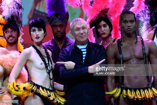 French fashion designer JeanPaul Gaultier flanked by US model Anna Cleveland poses at the end of a preview of his Fashion freak show at the Folies...