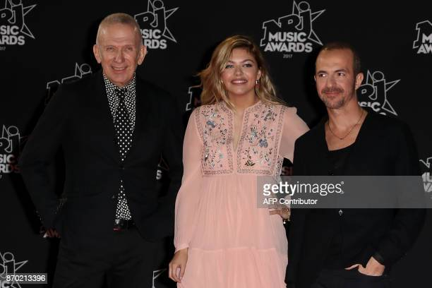 French fashion designer JeanPaul Gaultier French singer Anne Peichert aka Louane and French singer Calogero pose upon their arrival to attend the...