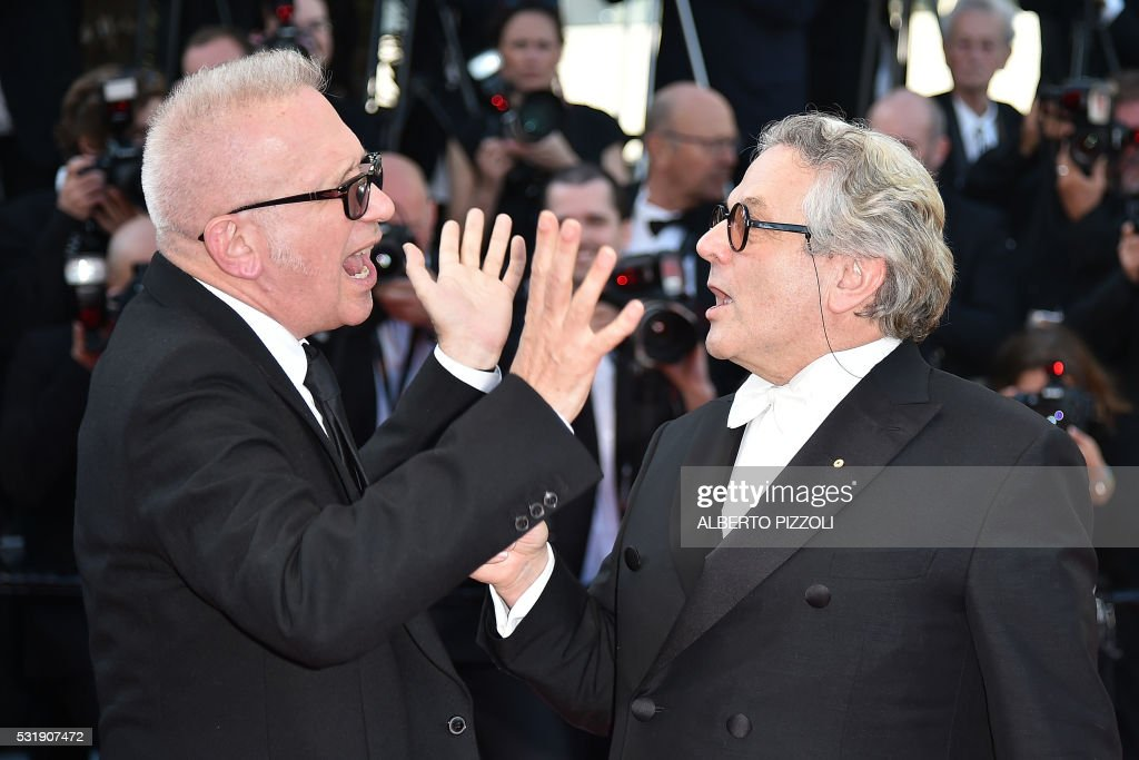 TOPSHOT - French fashion designer Jean-Paul Gaultier (L) jokes with Australian director and President of the Jury George Miller as they arrive on May 17, 2016 for the screening of the film 'Julieta' at the 69th Cannes Film Festival in Cannes, southern France. /