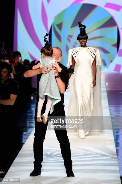 French fashion designer JeanPaul Gaultier kisses Ioni Conran the daughter of Model Coco Rocha at the end of the 2018 spring/summer Haute Couture...
