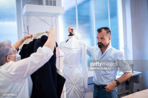 French fashion designer Julien Fournie adjusts a dress with his employee in his workshop in Paris, on June 18, 2020.