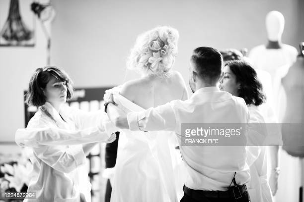 French fashion designer Julien Fournie adjusts the dress of his model Michaela Tomanova during the shooting of a film designed in place of the...