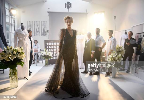 French fashion designer Julien Fournie and his model Michaela Tomanova pose during the shooting of a film designed in place of the fashion show on...