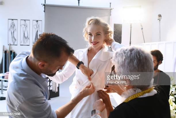 French fashion designer Julien Fournie and his workshop premiere, Madame Jacqueline are pictured with model Michaela Tomanova during the shooting of...