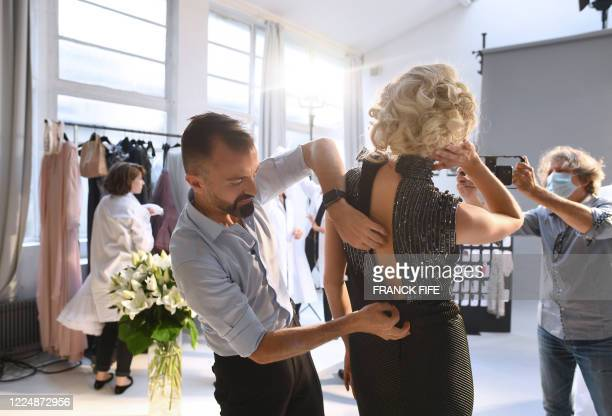 French fashion designer Julien Fournie is pictured with model Michaela Tomanova during the shooting of a film designed in place of the fashion show...