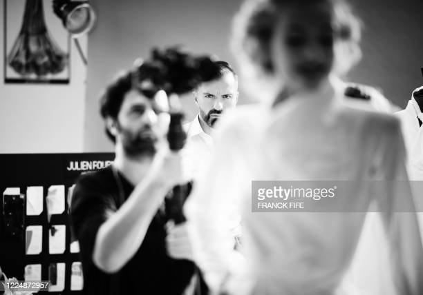 French fashion designer Julien Fournie looks as his model Michaela Tomanova during the shooting of a film designed in place of the fashion show on...