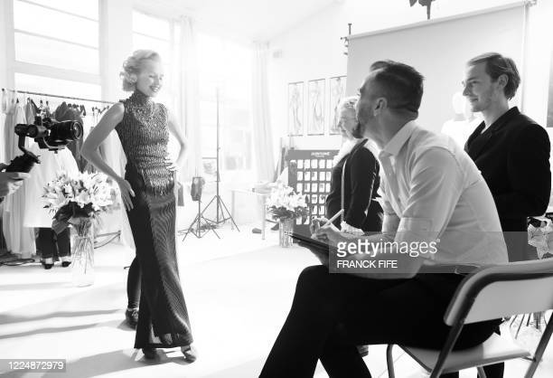 French fashion designer Julien Fournie looks as his model Michaela Tomanova takes part in the shooting of a film designed in place of the fashion...