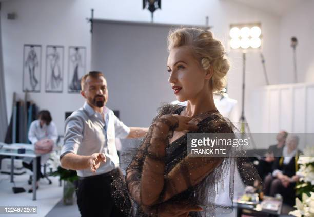 French fashion designer Julien Fournie poses with his Czech model Michaela Tomanova during the shooting of a film designed in place of the fashion...