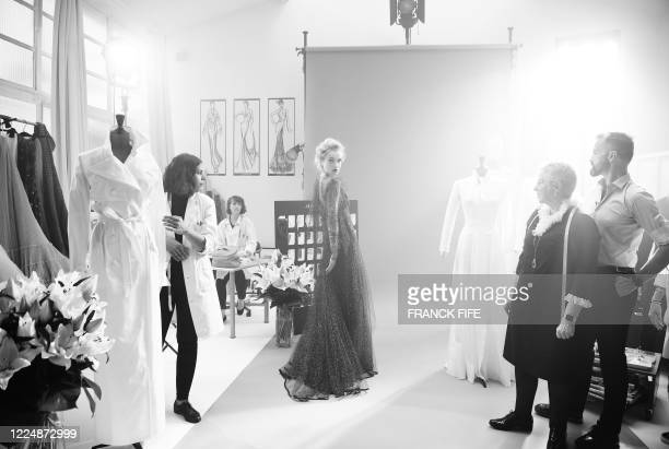 French fashion designer Julien Fournie poses with his Czech model Michaela Tomanova wearing a lace dress embroidered with 1940 sequins during the...