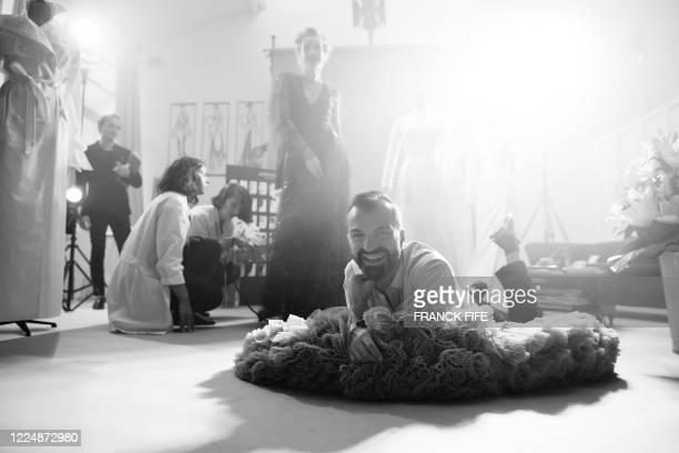 French fashion designer Julien Fournie poses with his model Michaela Tomanova and a lace dress embroidered with 1940 sequins during the shooting of a...