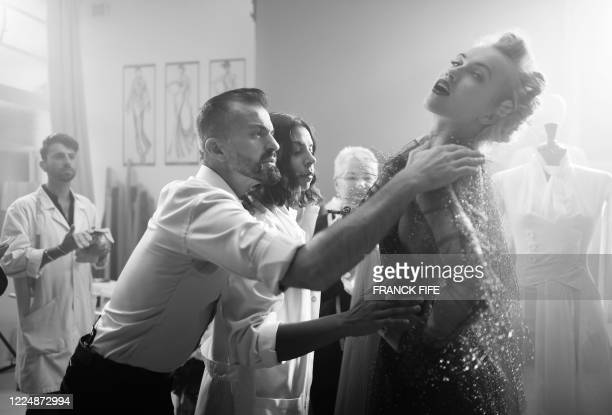 French fashion designer Julien Fournie poses with his model Michaela Tomanova wearing a lace dress embroidered with 1940 sequins during the shooting...