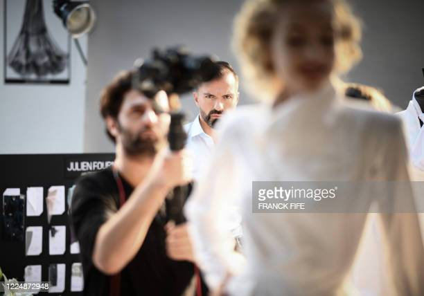 French fashion designer Julien Fournie watches his model Michaela Tomanova during the shooting of a film designed in place of the fashion show on...