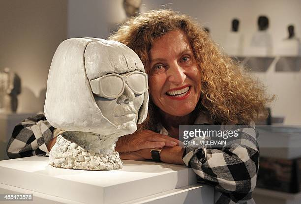 French fashion designer Nicole Farhi poses for pictures with her sculpture of editor of US vogue magazine Anna Wintour during a photocall in London...