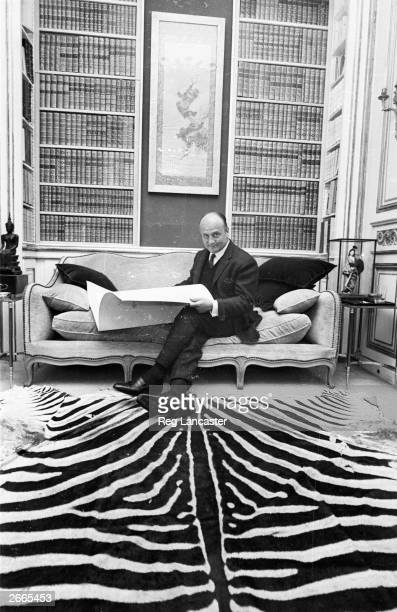 French fashion designer Pierre Balmain looks through a portfolio in his Parisian fashion house The floor is covered with a luxuriant zebra skin rug