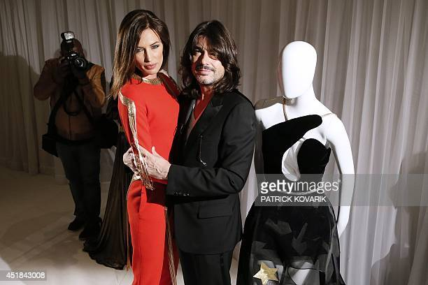 French fashion designer Stephane Rolland poses with Spanish model Nieves Alvarez during the 2014/2015 Haute Couture Fall-Winter collection...