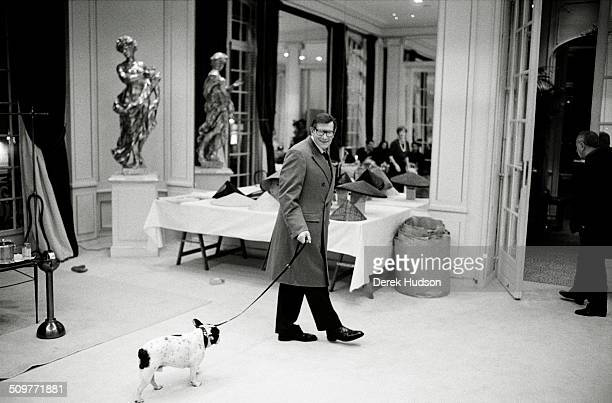 French fashion designer Yves Saint Laurent leads a dog on a leash during preparations for a fashion show Paris France 2005