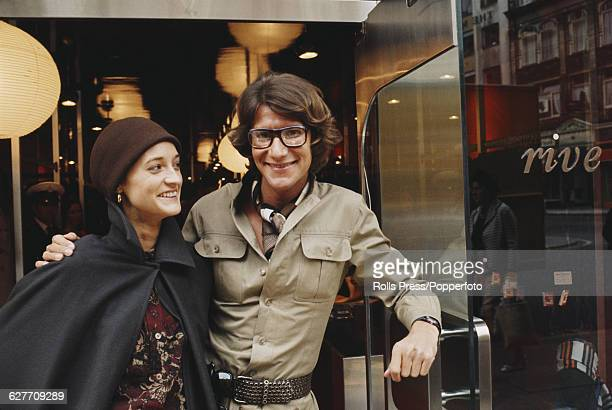 French fashion designer Yves Saint Laurent pictured with the model Loulou de la Falaise in the door way of his new 'Rive Gauche' boutique in Bond...