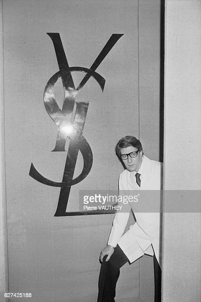 French fashion designer Yves Saint Laurent poses next to his fashion house logo during his 1982 haute couture SpringSummer fashion show in Paris...