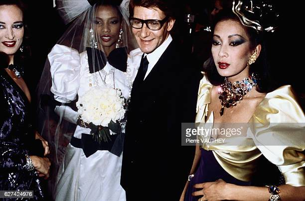 French fashion designer Yves Saint Laurent poses with his models during a fallwinter 19821983 haute couture women's fashion show The models are...