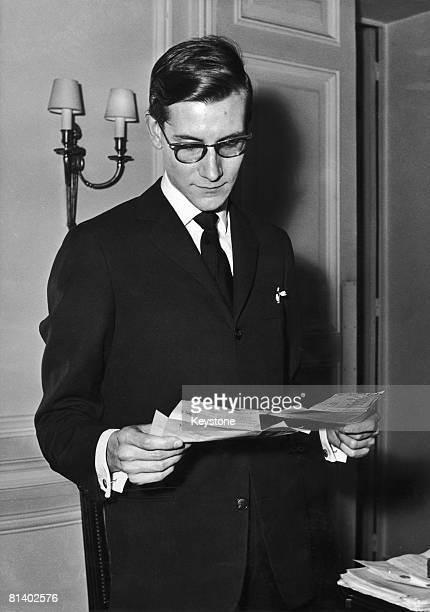French fashion designer Yves Saint Laurent reading trelegrams of congratulation after the success of his new spring and summer collection for Dior...