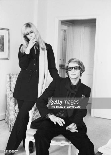French fashion designer Yves Saint Laurent seated and Betty Catroux standing Saint Laurent's celebrated muse pose for a portrait at a press event for...