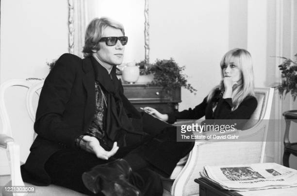 French fashion designer Yves Saint Laurent, seated, , and Betty Catroux, standing, Saint Laurent's celebrated muse, pose for a portrait at a press...