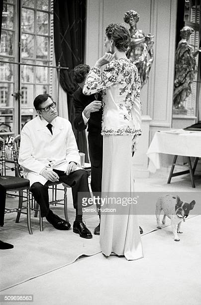 French fashion designer Yves Saint Laurent watches as an assistant adjusts a model's outfit during preparations for a fashion show Paris France 2005