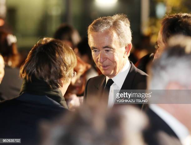 French fashion giant LVMH group CEO Bernard Arnault chats with Fendi CEO Pietro Beccari as they enjoy Dior's 2017 springsummer haute couture...