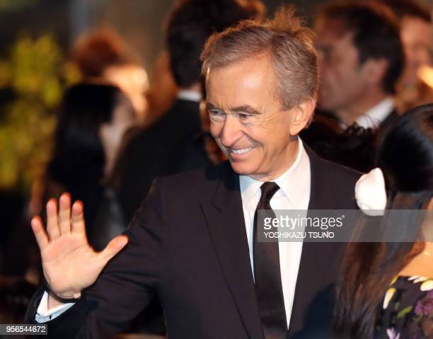 French fashion giant LVMH group CEO Bernard Arnault smiles as he enjoyed Dior's 2017 springsummer haute couture collection at the rooftop of the...