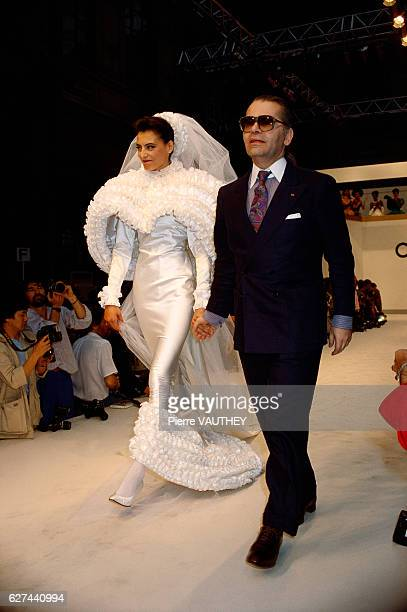 French fashion model Ines de la Fressange walks with German fashion designer Karl Lagerfeld in his haute couture wedding dress for French fashion...