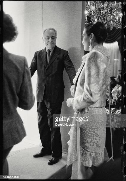 French fashion patron Pierre Berge inspects an unidentified model in the wings at an Yves Saint Laurent haute couture runway show at the Hotel...