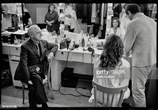 French fashion patron Pierre Berge sits backstage at a makeup table with a model during preparations for an Yves Saint Laurent haute couture runway...