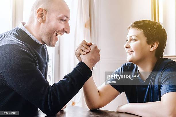 french father doing arm wrestling with son at home