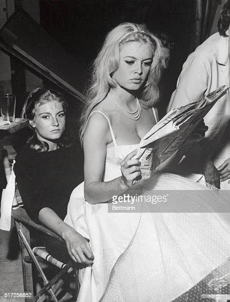 French film star Brigitte Bardot relaxes on the lap of her sister Mikanou as she takes time out to glance through a newspaper on the set of her...