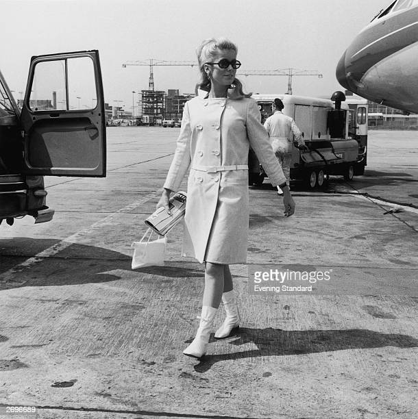 French film star Catherine Deneuve arriving at London airport She is wearing a white square cut coat by Andre Courreges with flat white boots