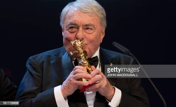 French filmmaker and journalist Claude Lanzmann holds his trophy after receiving the Honorary Golden Bear during the 63rd Berlinale Film Festival in...