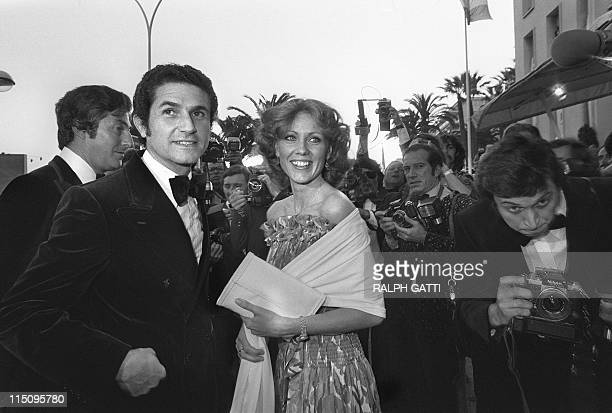 French filmmaker Claude Lelouch and an unidentified lady, surrounded by press photographers, pose on May 13, 1977 during Cannes Film Festival. AFP...