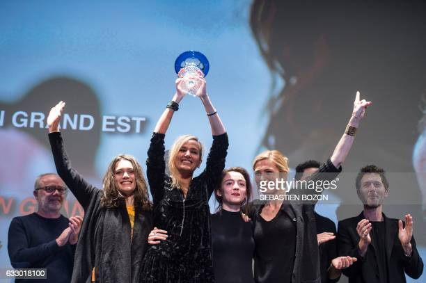 French filmmaker Julia Ducournau holds up the jury trophy flanked by French actresses Garance Marillier , Ella Rumpf , and Julie Gayet during the...