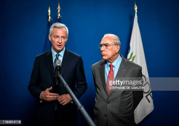 French Finance and Economy Minister Bruno Le Maire flanked by the Organisation for Economic Cooperation and Development Secretary General Jose Angel...