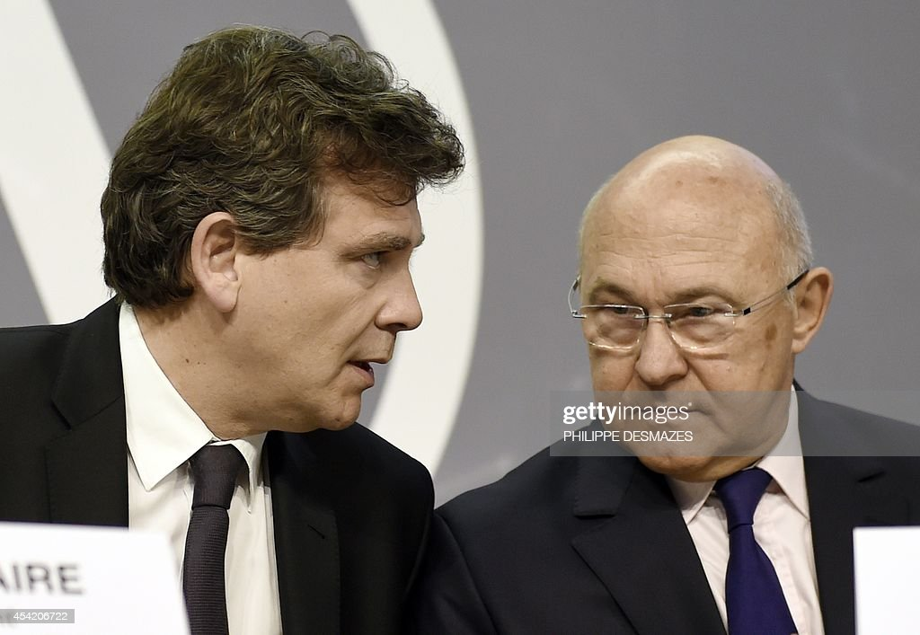 French Finance minister Michel Sapin (R) and Economy minister Arnaud Montebourg (L) talk during a meeting during a meeting on European Financing of companies on April 22, 2014, in Brignais near Lyon.